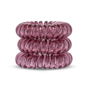 A tower of 3 maroon red coloured hair bobbles called spirabobbles. A red plastic spiral circular hair tie spira bobble