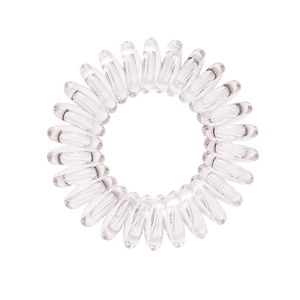 A see through clear coloured plastic circular hairband on a white background that looks like an old fashioned curly coiled telephone cable or a coiled spring which has been made into a circular shape