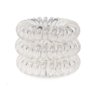 A tower of 3 transparent clear coloured hair bobbles called spirabobbles. A clear plastic spiral circular hair tie spira bobble.