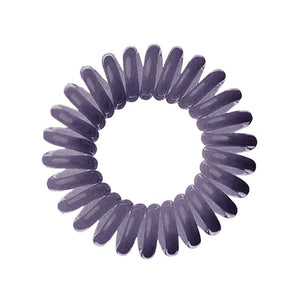 A dark grey solid coloured plastic circular hairband on a white background that looks like an old fashioned curly coiled telephone cable or a coiled spring which has been made into a circular shape