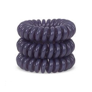 A grey solid coloured plastic circular hairband on a white background that looks like an old fashioned curly coiled telephone cable or a coiled spring which has been made into a circular shape