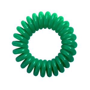 A green coloured plastic spiral circular hair bobble on a white background called a spirabobble.