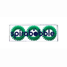 Load image into Gallery viewer, A flat transparent box of 3 green dream coloured hair accessories called spirabobble