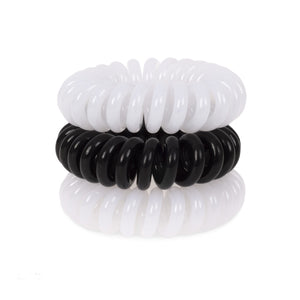 A tower of 3 black and white coloured hair bobbles called spirabobbles. A plastic spiral circular hair tie spira bobble.