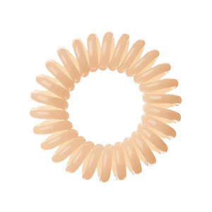 A Perfectly Peach coloured plastic spiral circular hair bobble on a white background called a spirabobble.