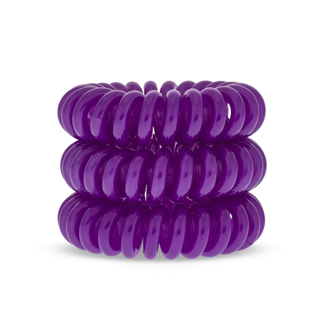 A tower of 3 purple berry coloured hair bobbles called spirabobbles. A beige plastic spiral circular hair tie spira bobble.