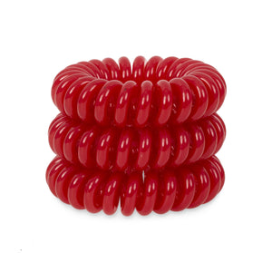 A tower of 3 red coloured hair bobbles called spirabobbles. A plastic spiral circular hair tie spira bobble.