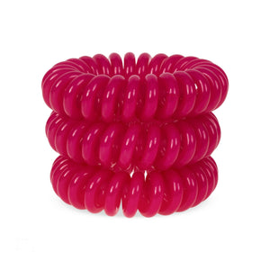 A tower of 3 rose pink coloured hair bobbles called spirabobbles. A plastic spiral circular hair tie spira bobble.