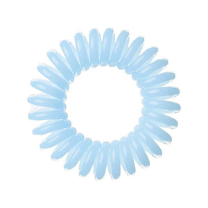A pale blue solid coloured plastic circular hairband on a white background that looks like an old fashioned curly coiled telephone cable or a coiled spring which has been made into a circular shape