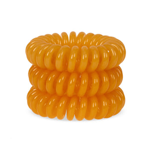 A tower of 3 Tangerine Orange coloured hair bobbles called spirabobbles. A plastic spiral circular hair tie spira bobble.