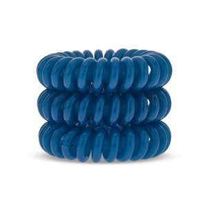 A tower of three (placed on top of each other) turquoise blue solid coloured plastic spiral circular hair bobbles on a white background that looks like an old fashioned curly coiled telephone cable or a coiled spring which has been made into a circular sh