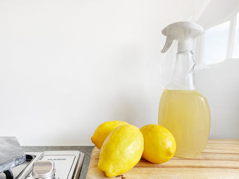 Lemons on a counter with a yellow spray bottle - How to make your kitchen sustainable.
