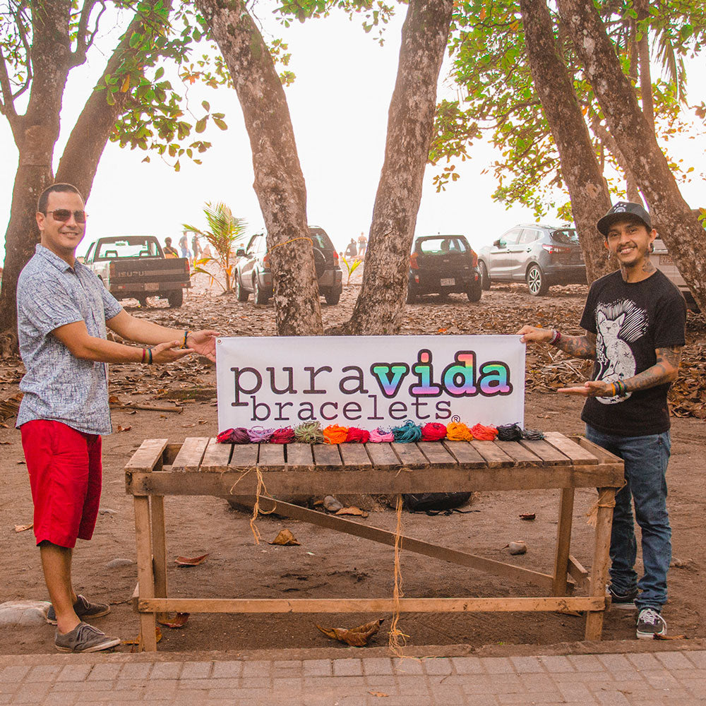 Two artisans with Pura Vida's first logo