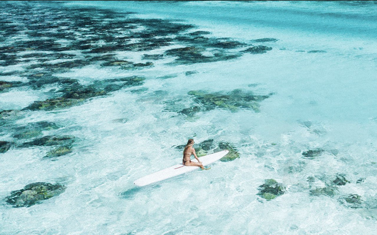 Surfer sitting on surfboard in clear ocean water