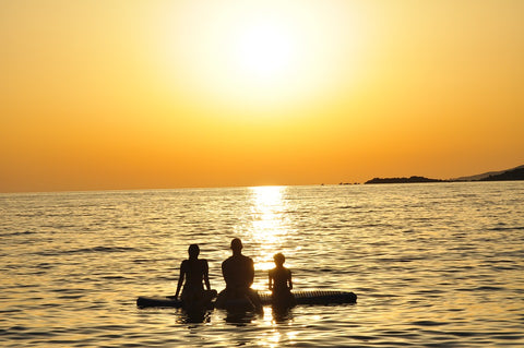 Family on an SUP at sunset