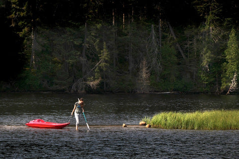 Woman Pulling Kayak Over Shallow Water