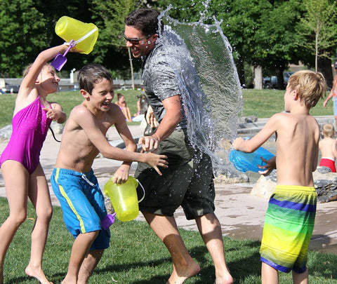 kids splashing adult with water