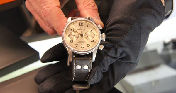 Gloved hand holding Hamilton Khaki Harrison Ford Wrist Watch silver dial with brown band and stainless steel case