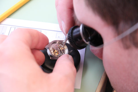 Watchmaker looking through loop on open movement
