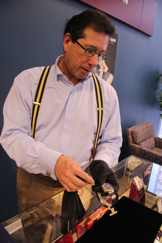 Salesman showing a Ulysse Nardin watch with black gloves on standing over a display case
