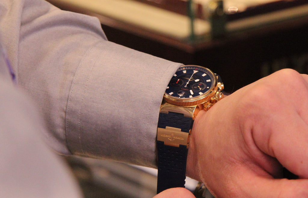 Man with shirt cuff putting Ulysse Nardin Watch on