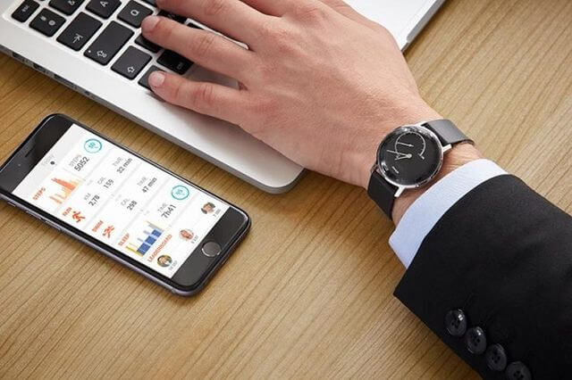 Smart phone next to hand with watch typing on computer