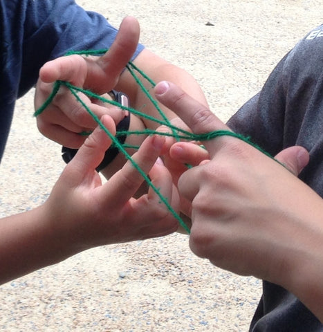 children's hands as they play Cat's Cradle, a string game