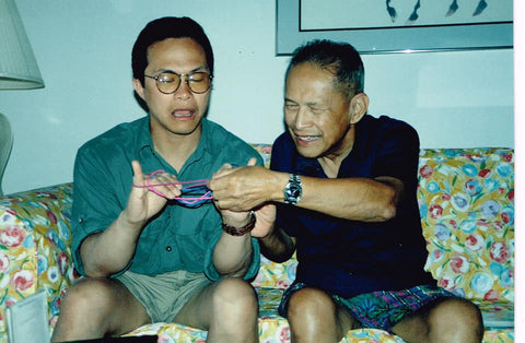 Adult father and son playing Cat's Cradle, a universally beloved string game