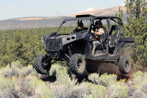 Custom UTV for military use flies over a hill.