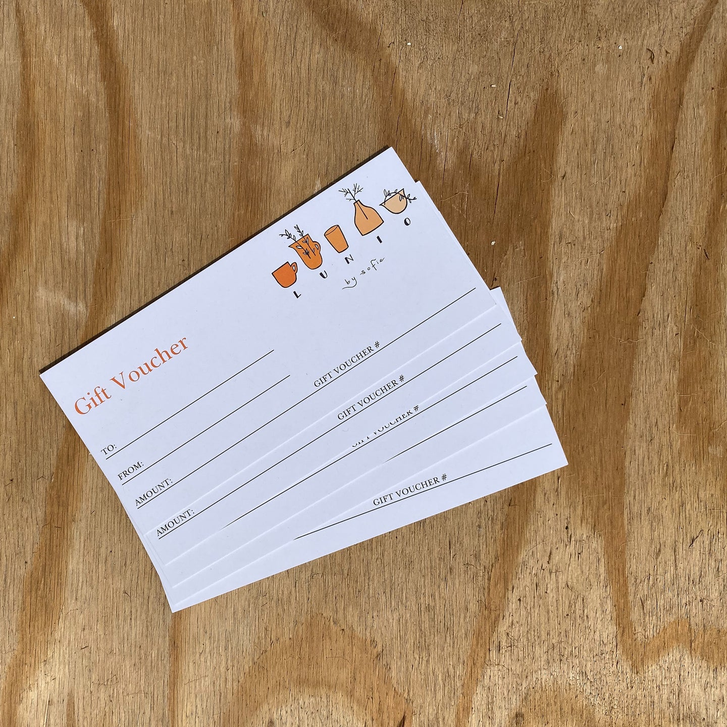 A blank paper gift voucher with the Lunio by Sofie logo, resting on a piece of pale wood.