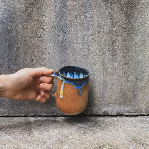 A handmade ceramic mug, held up against a concrete wall by a single hand. Made from light brown Australian stoneware clay with a blue, brown and white glaze inside and blue drips down the outside.