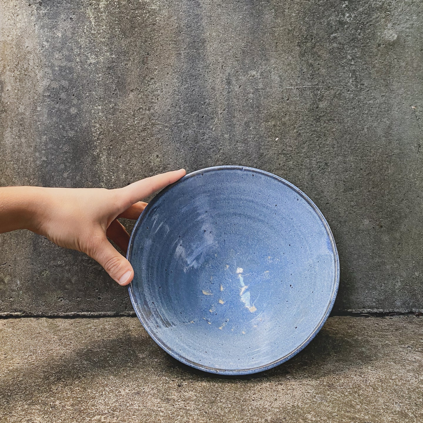 A handmade ceramic bowl, with a single hand holding the piece up against a concrete wall. Made from white Australian stoneware clay with a sky blue glaze on the inside and a blue and brown glaze outside.