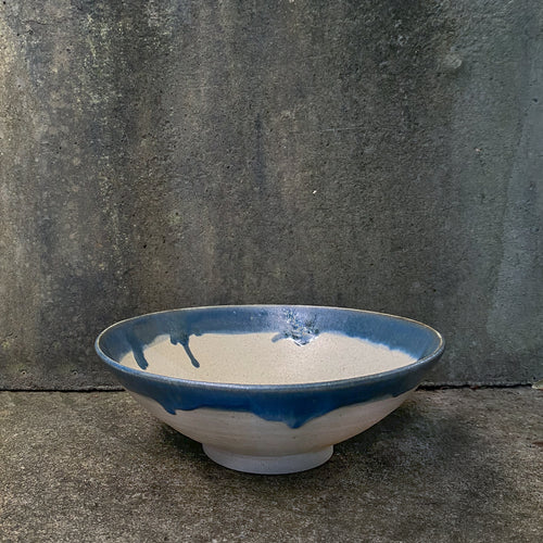 A handmade ceramic serving bowl sitting against a concrete wall. Made from speckle Australian stoneware clay with a cream matte glaze and indigo glaze around the rim.
