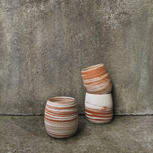 A handmade ceramic tumbler, sitting against a concrete wall. Made from white and terracotta Australian earthenware clay marbled together with a clear glaze inside and natural raw clay on the outside.