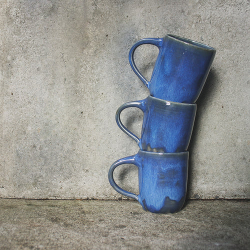 Three handmade ceramic mugs stacked on top of each other against a concrete wall. Made from white Australian stoneware clay mottled blue glaze.