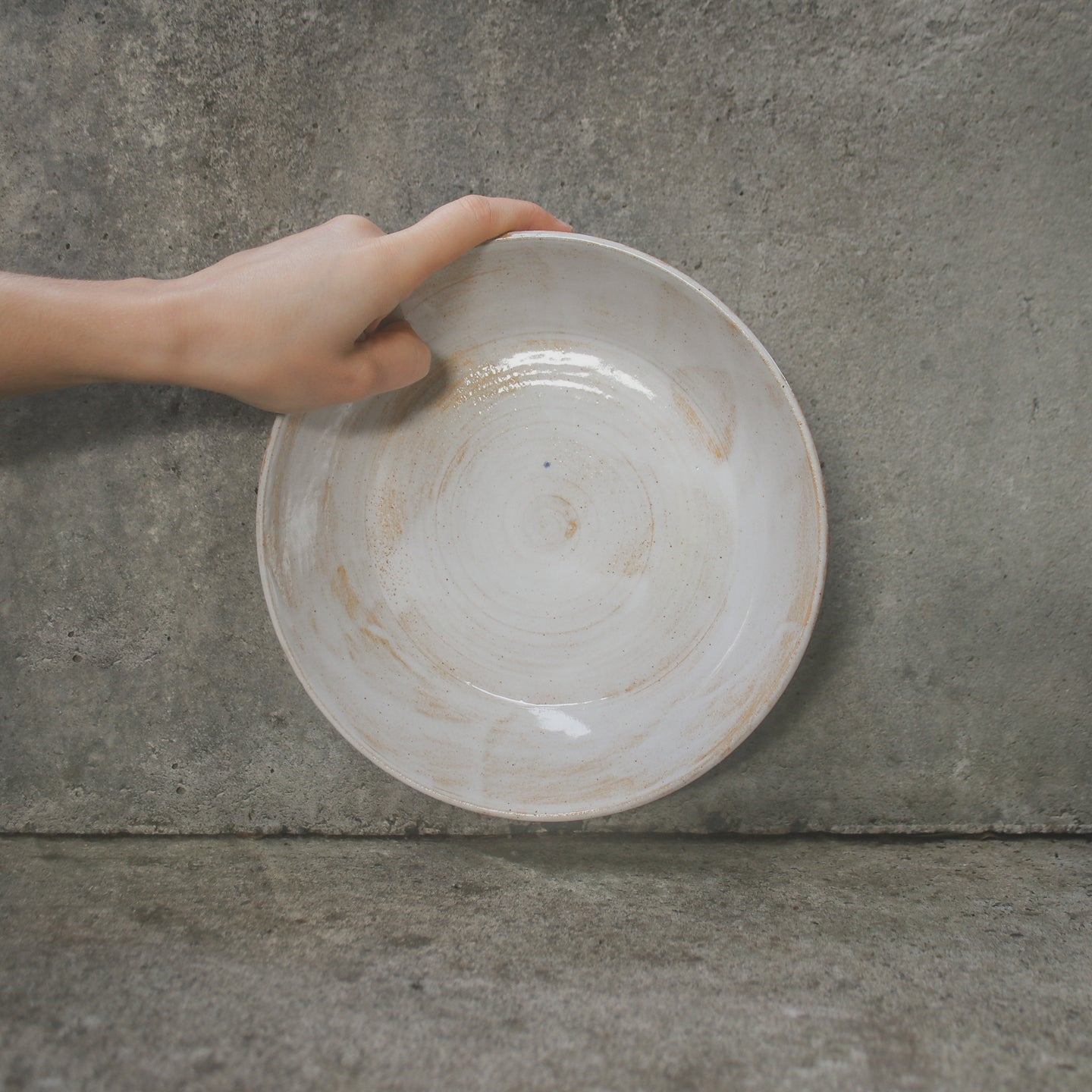 A handmade ceramic serving bowl being held up by a single hand against a concrete wall. Made from buff Australian stoneware clay with a white and subtle orange glaze.