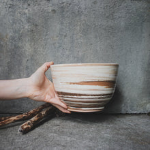 Load image into Gallery viewer, A large handmade ceramic bowl being held up by a single hand against a concrete wall. Made from white, terracotta and brown Australian earthenware clay with a clear glaze.