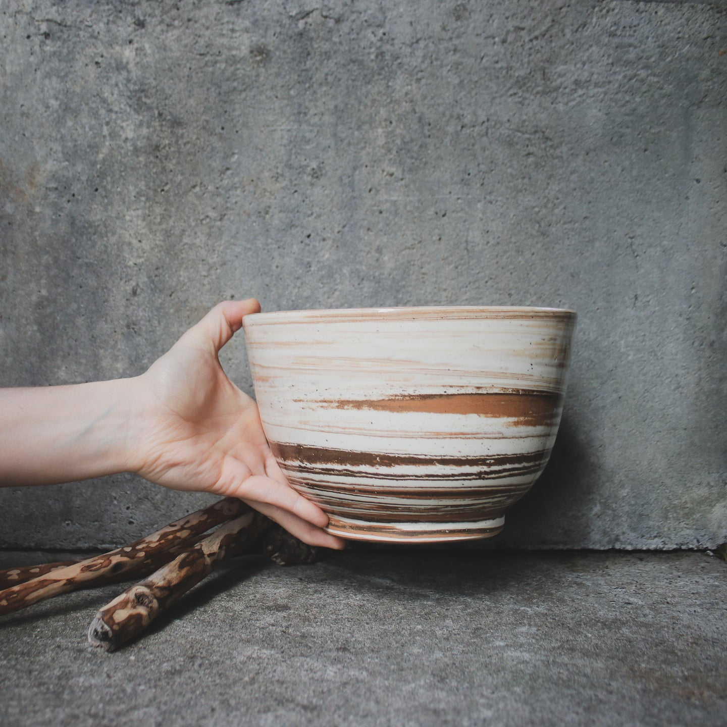 A large handmade ceramic bowl being held up by a single hand against a concrete wall. Made from white, terracotta and brown Australian earthenware clay with a clear glaze.