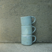 Load image into Gallery viewer, A stack of three handmade ceramic mugs sitting against a concrete wall. Made from white Australian stoneware clay with a turquoise matte glaze outside and a cream matte glaze inside.