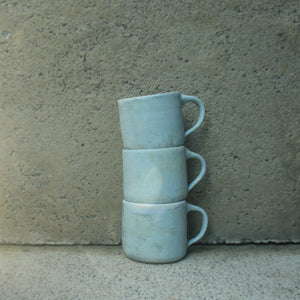 A stack of three handmade ceramic mugs sitting against a concrete wall. Made from white Australian stoneware clay with a turquoise matte glaze outside and a cream matte glaze inside.