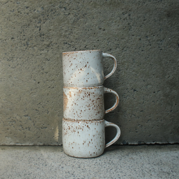 Three handmade ceramic mugs stacked on top of each other against a concrete wall. Made from buff speckled Australian stoneware clay with a white and orange glaze.