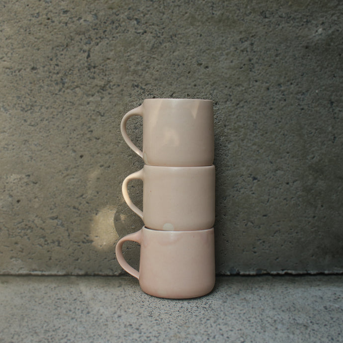 Three handmade ceramic mugs, stacked against a concrete wall. Made from white Australian stoneware clay with a pink satin matte glaze.