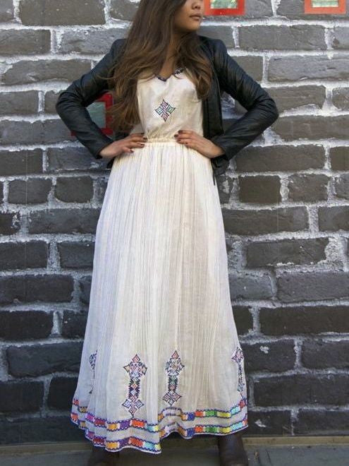 White, sleeveless traditional Ethiopian dress with multicolored cross embroidered motif