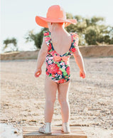 charlarue kids RuffleButts Sunset Garden Ruffle One Piece Swimsuit rear view of ruffles and bow girl on beach in sun hat