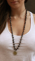 Beaded necklace with fresh water black pearls and a foreign coin pendant