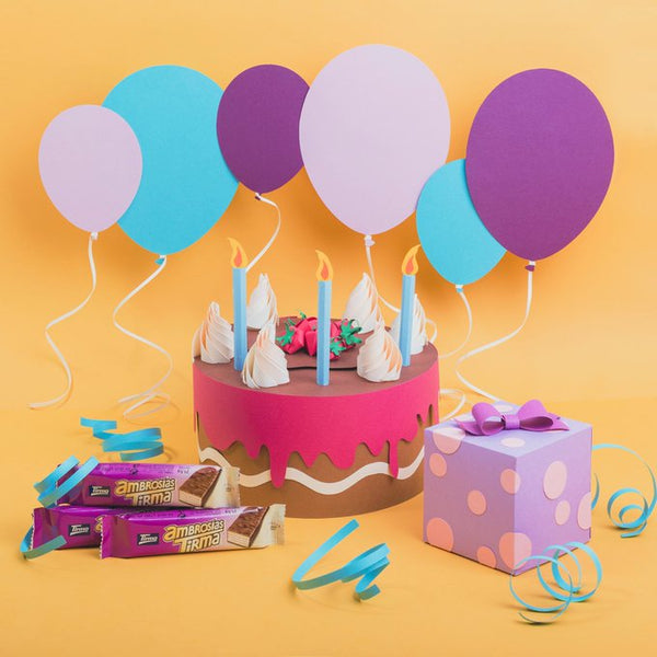 Paper cutouts of a cake, paper balloons, paper gift and confetti with Tirma milk chocolate wafers