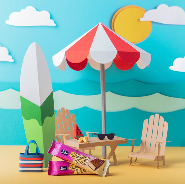 Paper cut out of a beach setting with a beach umbrella, surf board and sunglasses with Milk Chocolate Wafers