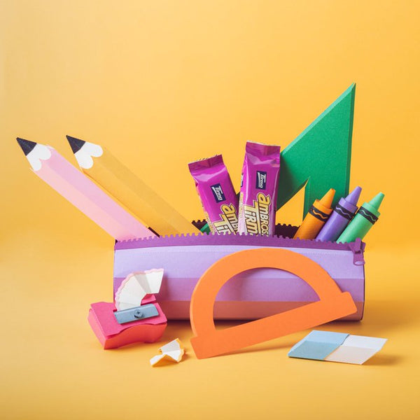 Paper cut out of a pencil case with stationery including a green ruler and an orange protactor with Tirma Milk Chocolate Wafers