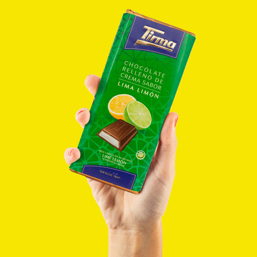 Tirma Chocolate filled with Lime and Lemon Flavoured Cream. Holding Tirma chocolate in hand with yellow background. Made in Spain. Available in UK