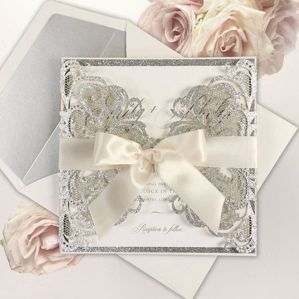 Silver Glitter Luxury Gatefold Laser cut Set Wedding Invitation with a Cream Pearlised Ribbon and Matching Silver lined Envelope.